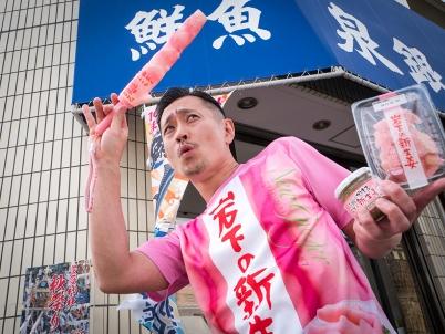 画像:岩下の新生姜Tシャツを着た、フィッシュロックバンド「漁港」森田釣竿氏@鮮魚店「泉銀」