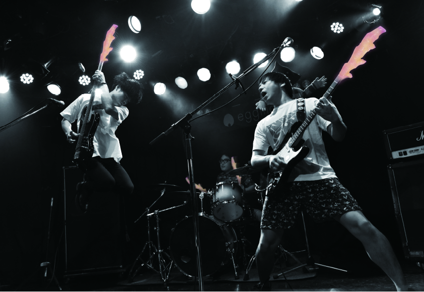 画像:岩下の新生姜×SAKANAMON コラボTシャツ フロントデザイン(一本丸ごとの岩下の新生姜をSAKANAMONメンバーの楽器と組み合わせた迫力あるステージショット)